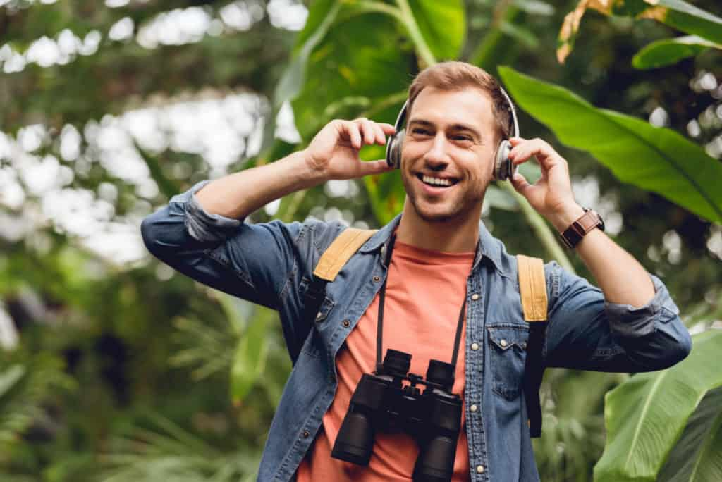 Guy listening to headphones in the rain forest