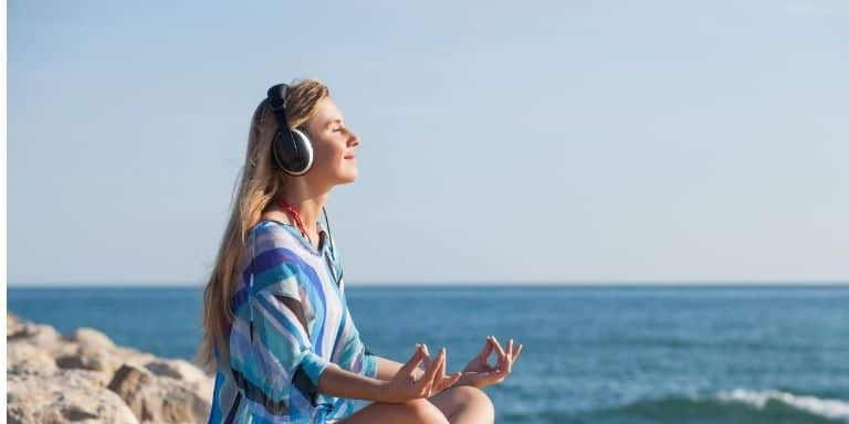 Woman meditating with over-ear headphones