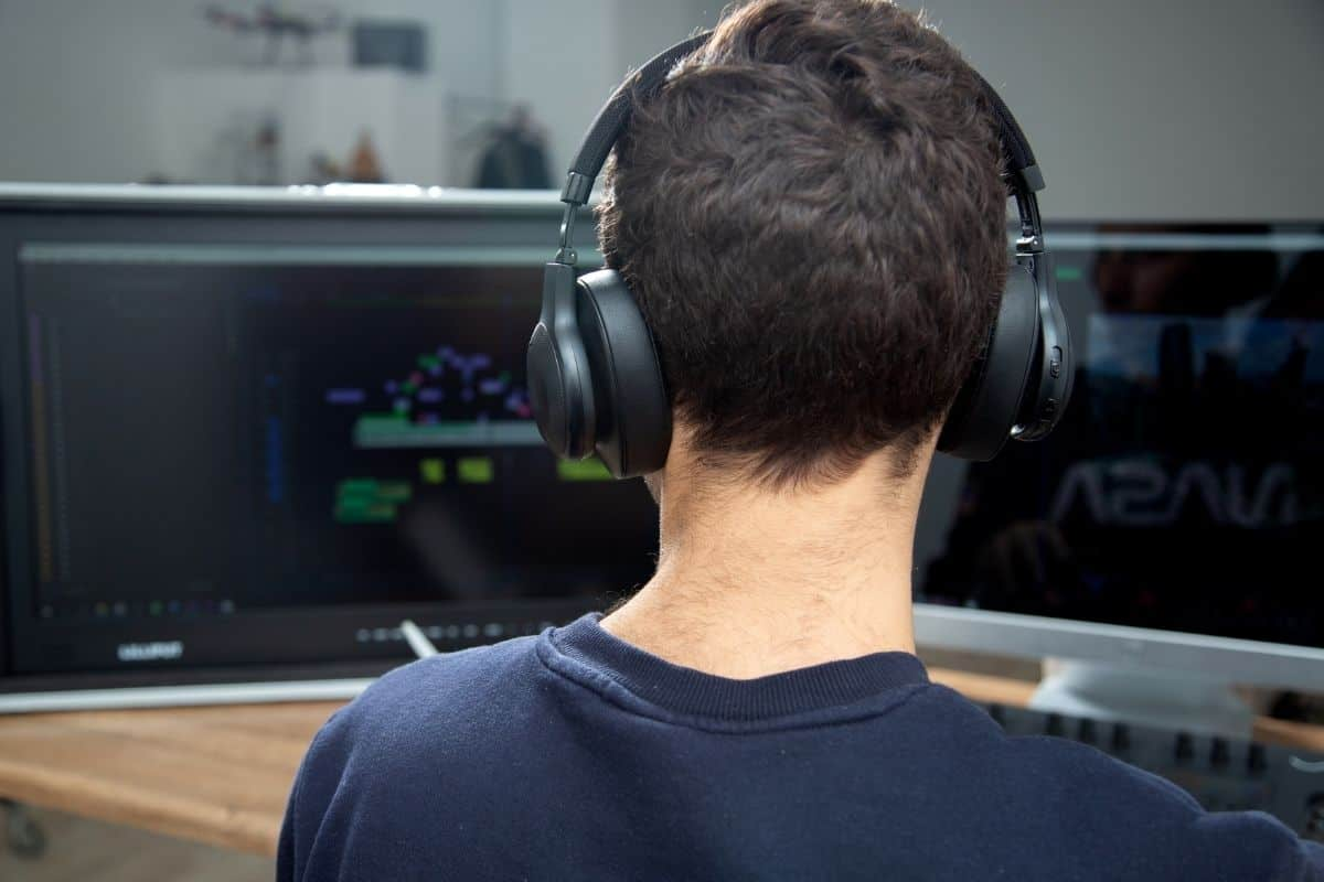 A man with wireless headset playing a game on the PC