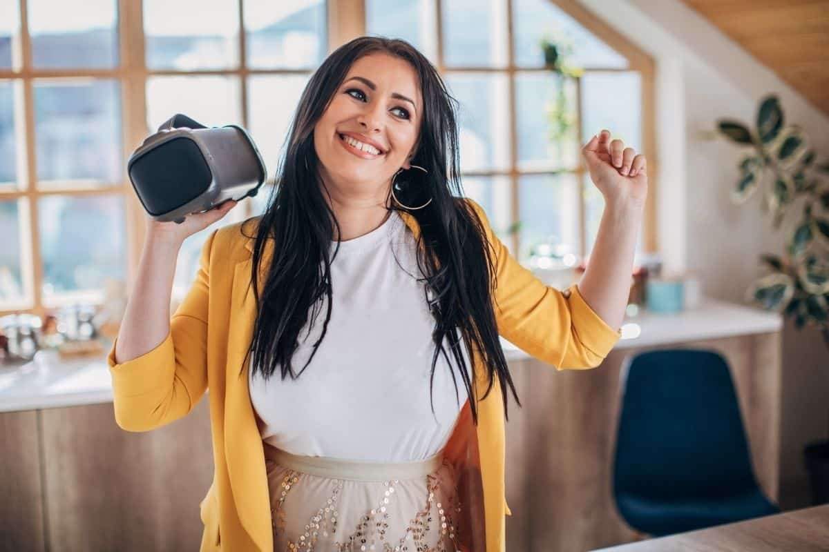 Woman dancing with a wireless speaker in her hand