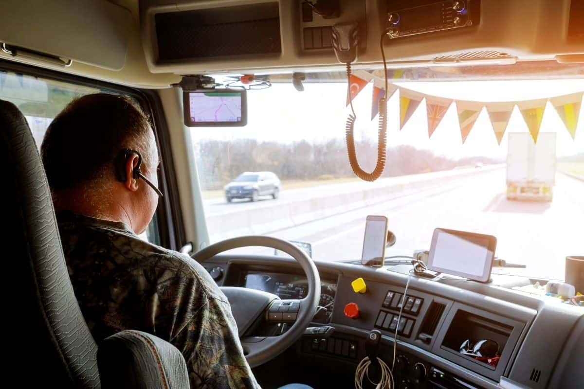 A trucker driving with a headset in his ear